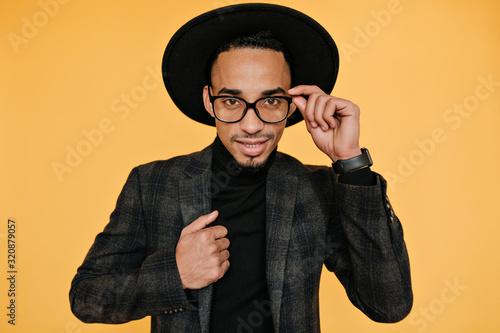 Studio portrait of handsome brown-eyed male model playfully touching his hat Canvas-taulu