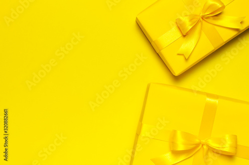 Two Bright yellow gift present box with ribbon and bow on yellow background top view copy space. Flat lay holiday background. Birthday present, March 8, Mother's Day, Valentine's Day. Congratulation