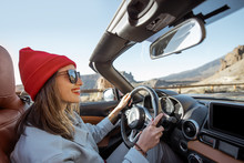 Happy Woman In Red Hat Driving Convertible Car While Traveling On The Desert Road. Carefree Lifestyle And Travel Concept