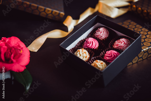 Close up open box with delicious allsorts chocolate sweets with multicolored cream filling, pink rose and golden satin ribbon on black background Wallpaper Mural