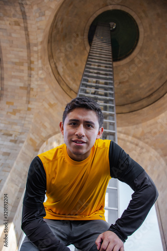 From below a man looking at the camera in a huge architectonic structure Wallpaper Mural