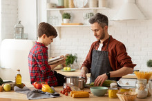 Father Son Cooking Together By Recipe In Cookbook