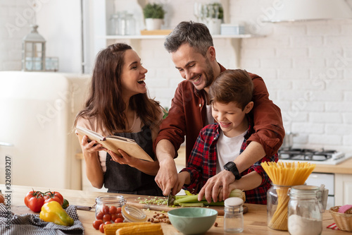 Happy family laughing loud and cooking on kitchen Fotobehang