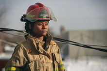 Women Firefighter With Red Helmet Standing Outside