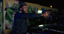 Side View On African American Young Cop Pointing Gun At Somebody Outdoors At Night. Police Officer Arresting Somebody At Dark Street At His Car.