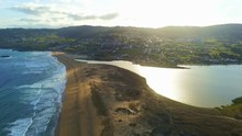 Drone Footage Of Beach And Lagoa Da Frouxeira Near Coastal City Of Valdovino In A Coruna, Spain During A Beautiful Sunset Reflecting Off The Lagoon Water. Camera Tracking Crane Downwards.