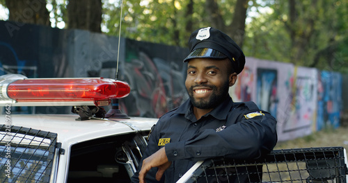 Obraz na plátne Portrait of handsome African American young policeman in uniform and cap