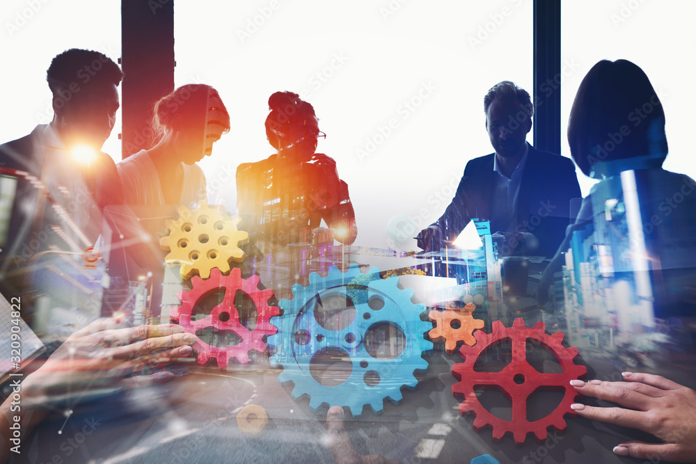 Fototapeta Businessmen that work together in office at night. Gears overlay. concept of teamwork and partnership. Double exposure