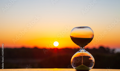 Fotografiet Hourglass at sunset or dawn on a blurry background, as a reminder of the passing