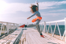 Hip Hop Dancer In Fashion Sportswear Jumping And Dancing In The Street
