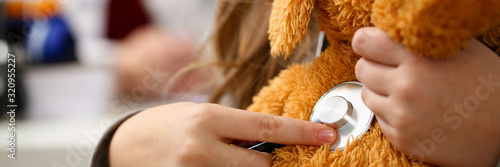 Carta da parati Female hand of little girl hold stethoscope listen heart bit concept closeup