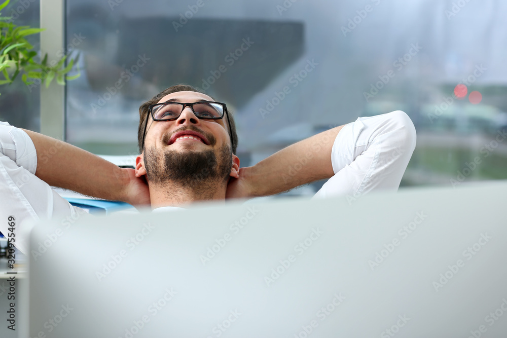 Fototapeta Handsome smiling bearded adult clerk person arms crossed up over head sit behind laptop pc display at office workplace desk portrait. Stress free home worker people optimistic cozy carefree pleasure