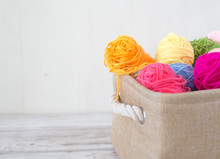 Bright Colored Threads For Knitting In A Basket On A Wooden Background