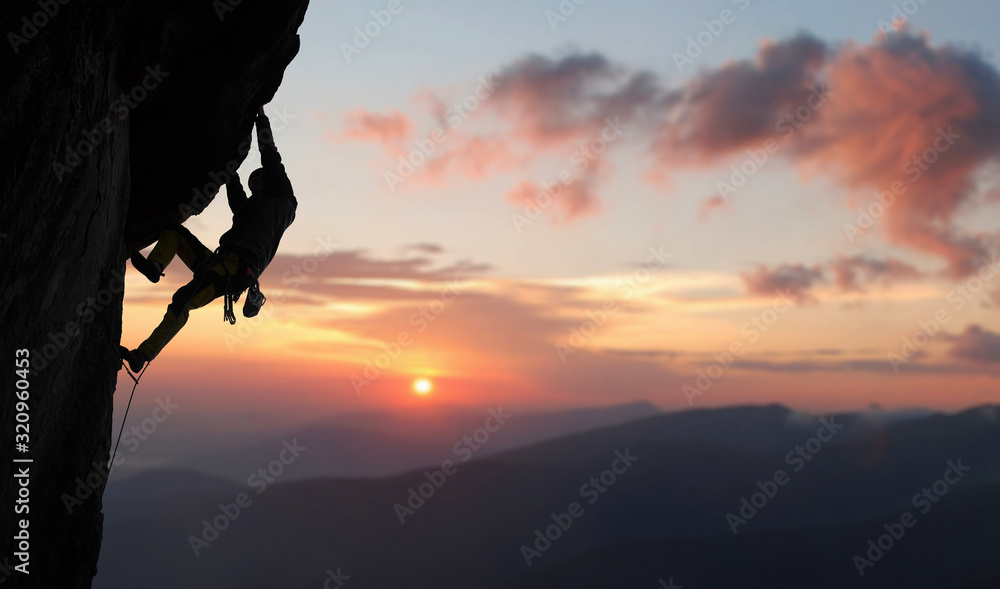 Fototapeta Male climber in rock climbing equipment, pulling up and doing next step on high cliff reaching rocky top. Side view. Panoramic view of mountains and amazing pink sky with sunset and clouds. Copy space