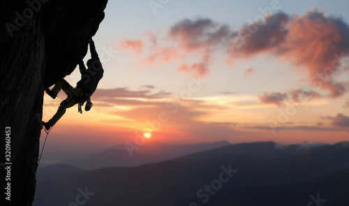 Fototapeta Male climber in rock climbing equipment, pulling up and doing next step on high cliff reaching rocky top. Side view. Panoramic view of mountains and amazing pink sky with sunset and clouds. Copy space obraz