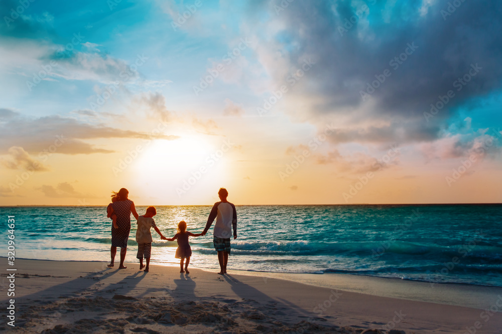 Fototapeta happy family with tree kids walk at sunset beach