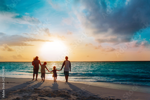 Obraz happy family with tree kids walk at sunset beach - fototapety do salonu