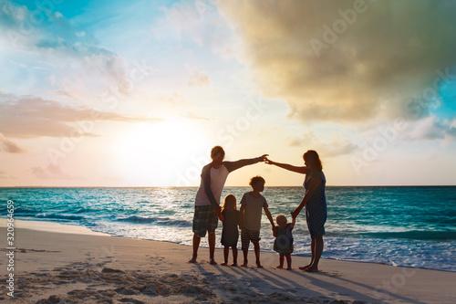 Fototapeta happy family with kids play at sunset beach obraz