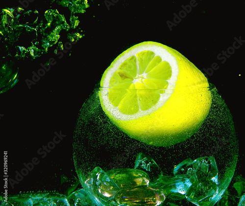 Photo Six segments of big yellow lemon and ice inside glassball with water air drop on