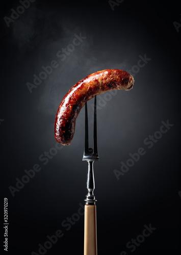 Fototapeta Grilled Bavarian sausage on a fork. obraz