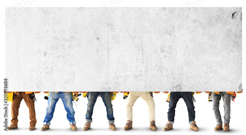 Fototapeta Builders with tools in construction clothing hold a heavy slab obraz