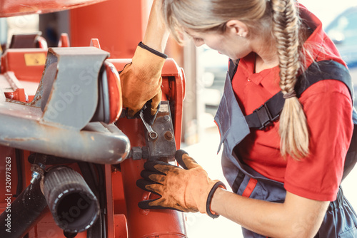 Woman machinist working with wrench of a farm machine - 320978263