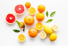 Fresh Citrus Background. Oranges, Grapefruits, Leaves - Whole Fruits And Halfs - On White Background Top-down