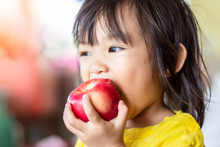 Portrait Image Of 1-2 Years Old Of Baby. Happy Asian Child Girl Eating And Biting An Red Apple. Enjoy Eating Moment. Healthy Food And Kid Concept.