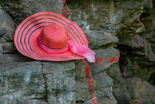A Bright And Rich Pink Hat With A Stripe Pattern And A Matching Satin Ribbon Bow Hangs On Large Stone Rocks In A Darkened Place With Sunlight.