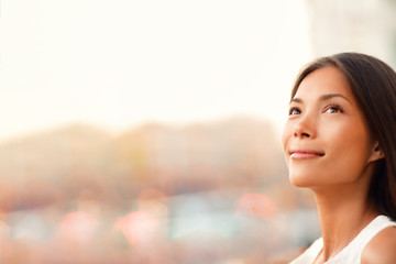 Happy young Asian woman natural beauty looking up pensive thinking of successful life and goal achievement, hopeful for the future career. Beautiful model with copy space.