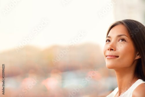 Fototapeta Happy young Asian woman natural beauty looking up pensive thinking of successful life and goal achievement, hopeful for the future career. Beautiful model with copy space. obraz