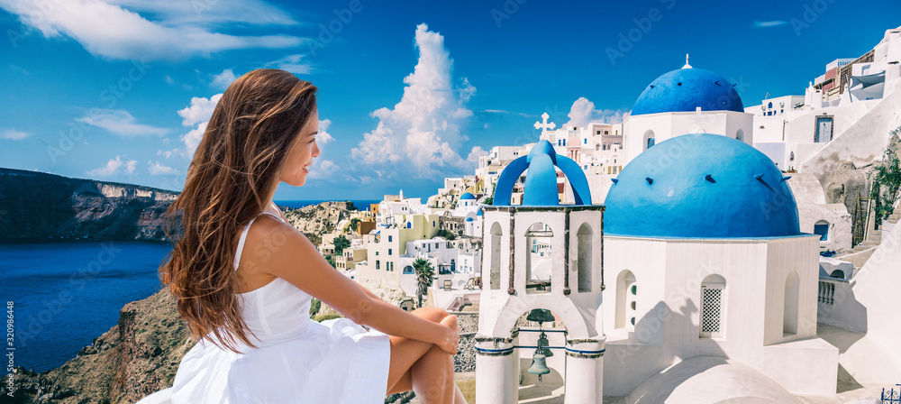 Fototapeta Travel Greece vacation luxury Europe cruise destination woman tourist panoramic of Santorini island. Asian lady in white dress looking at view of famous blue domes church panorama.