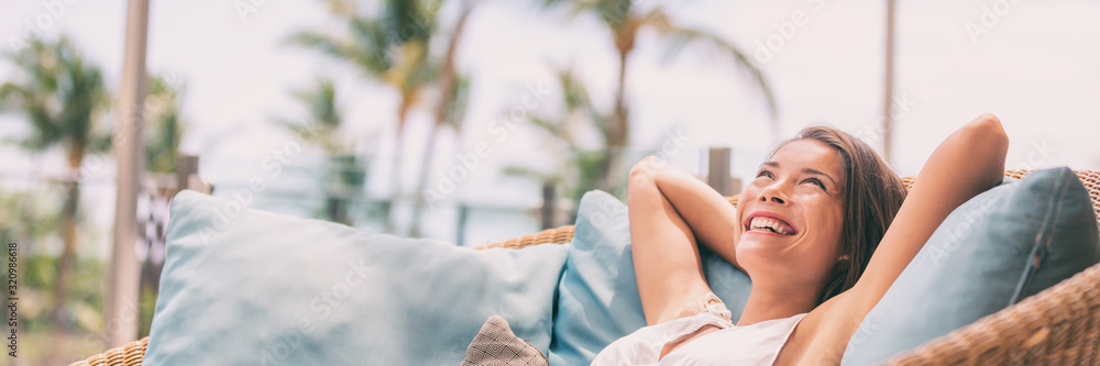 Obraz Lifestyle relax happy Asian woman on sofa luxury hotel living banner panoramic. Comfort home summer travel vacation free girl breathing clean air on summer destination panorama. fototapeta, plakat