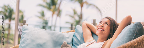 Obraz Lifestyle relax happy Asian woman on sofa luxury hotel living banner panoramic. Comfort home summer travel vacation free girl breathing clean air on summer destination panorama. - fototapety do salonu