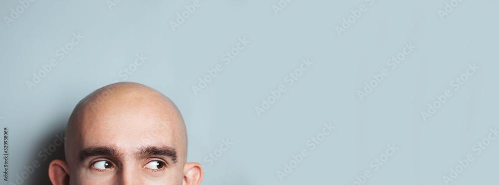 Fototapeta Emotional portrait of surprised bald man. half-face. Copyspace for text. Vertical.