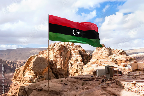 Flag of Islamic republic of Libya waving in mountain background