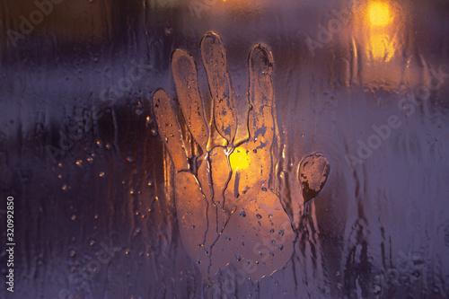 Obraz na plátně Slightly blurred handprint on a frozen window.
