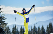 Cropped View Of Rejoicing Young Woman Posing And Showing Thumbs Up With Ski Poles In Hands Up. Panoramic View Of Winter Wooded Mountain Landscape On Blurred Background. Horizontal Portrait Shot.