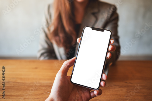 Obraz Mockup image of a woman holding and showing white mobile phone with blank black desktop screen to someone - fototapety do salonu