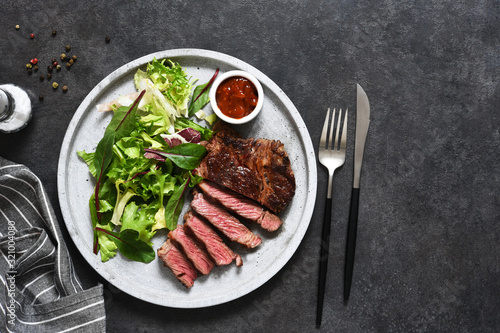 Fototapeta Grilled marbled beef steak with salad in a plate on the kitchen table. With copy space under the text. obraz
