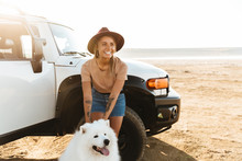 Woman Cuddle A Dog Samoyed Outdoors At The Beach
