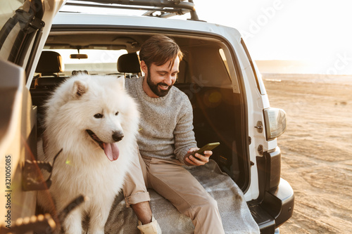 Man with dog samoyed outdoors at the beach Canvas Print