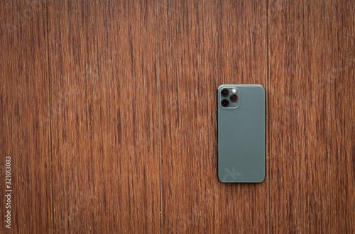 Fotografía back smartphone on wooden desktop. Top view