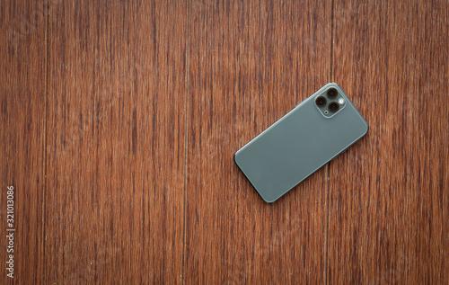 Fotomural back smartphone on wooden desktop. Top view