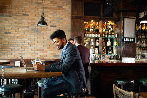 Handsome business man using laptop at his work break in restaurant
