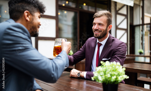 Having a pint with friend. Cheerful young men toasting with beer while sitting together at the bar