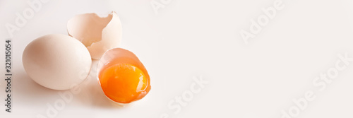 Foto Broken egg and egg yolk on white panoramic background with copy space
