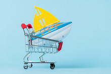 Small Shopping Trolley With Toy Boat On Blue, Leasing Concept