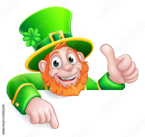 Fototapeta A Leprechaun St Patricks Day cartoon character giving a thumbs up, peeking over a sign and pointing at it obraz
