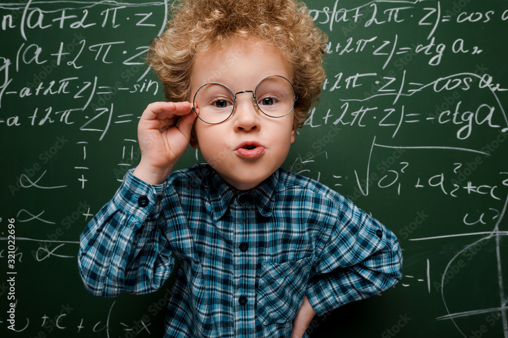 Fototapeta smart kid touching glasses and standing with hand on hip near chalkboard
